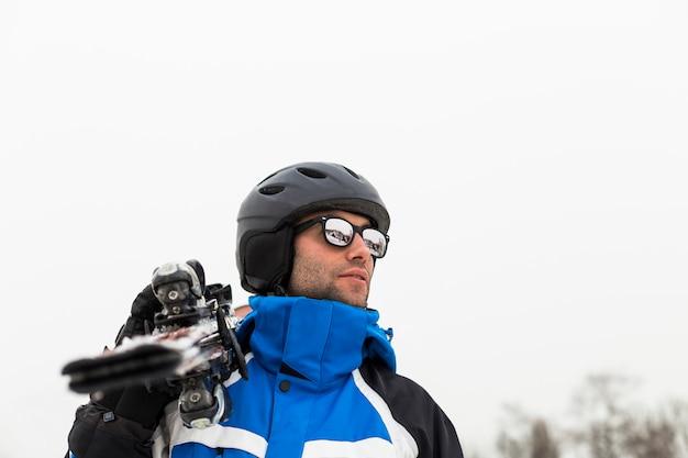 Uomo bello sciatore in cima alla montagna. nebbia. stagione invernale. sport e stile di vita sano
