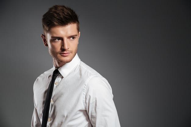 Uomo bello serio in camicia e cravatta in piedi