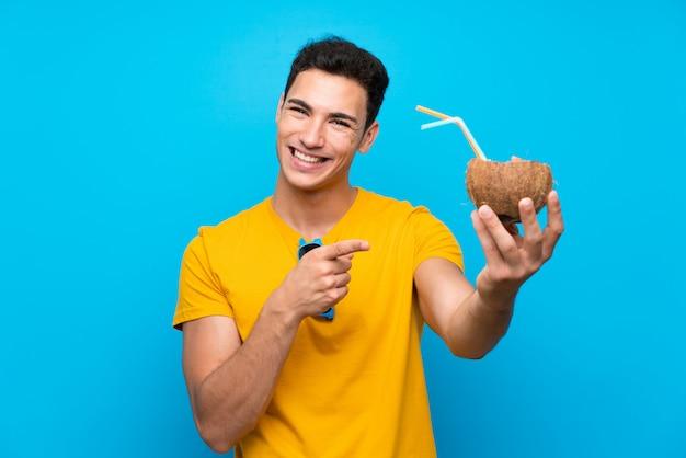 Uomo bello sopra fondo blu con una noce di cocco