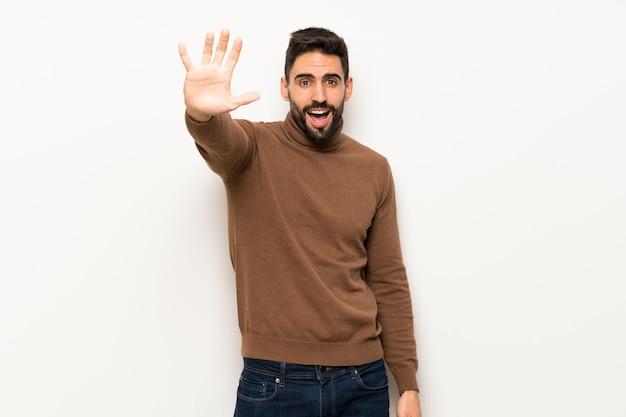 Uomo bello sopra la parete bianca che saluta con la mano con l'espressione felice