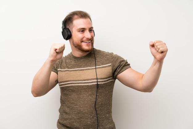Uomo bello sopra la parete bianca isolata che ascolta la musica con le cuffie