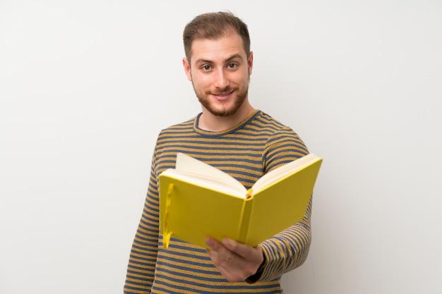 Uomo bello sopra la parete bianca isolata che tiene e che legge un libro