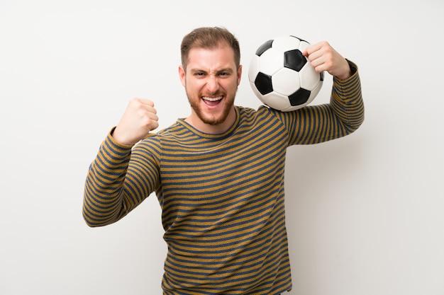 Uomo bello sopra la parete bianca isolata che tiene un pallone da calcio