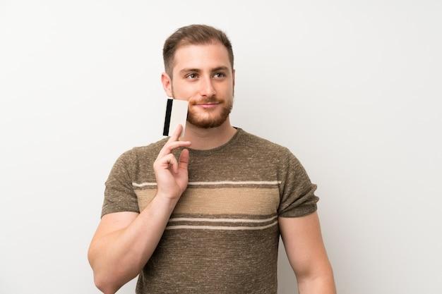 Uomo bello sopra la parete bianca isolata che tiene una carta di credito