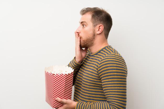 Uomo bello sopra la parete bianca isolata che tiene una ciotola di popcorn