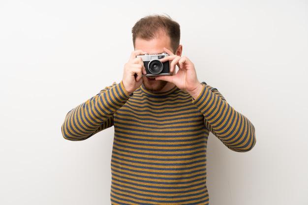 Uomo bello sopra la parete bianca isolata che tiene una macchina fotografica