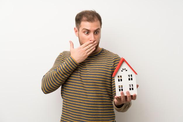 Uomo bello sopra la parete bianca isolata che tiene una piccola casa