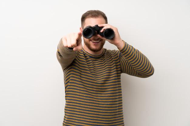 Uomo bello sopra la parete bianca isolata con il binocolo nero