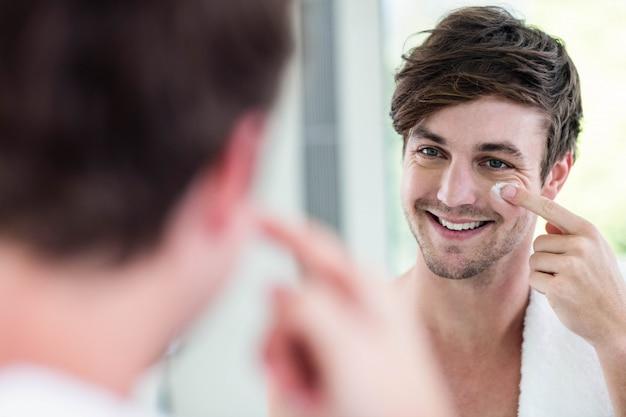 Uomo bello sorridente che applica crema in bagno