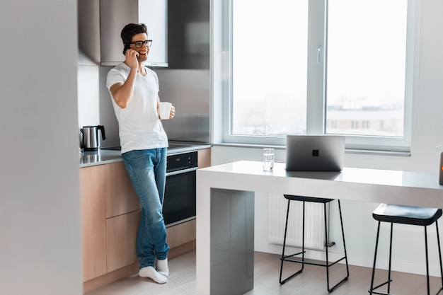 Uomo bello sorridente che parla sullo smartphone di mattina a casa