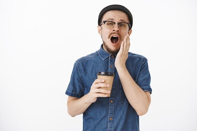 Uomo bello stanco assonnato con barba e baffi in occhiali e berretto alla moda che afferra la tazza di caffè di carta nella caffetteria vicino al lavoro mattina sbadigliando con la bocca aperta e l'espressione sognante