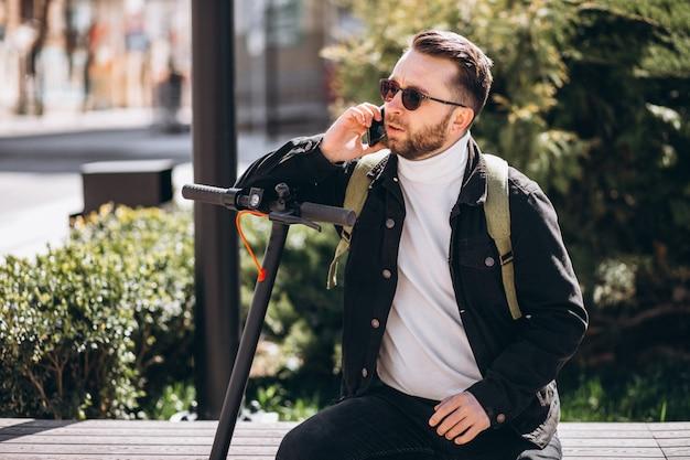 Uomo bello sul motorino che compera online sul telefono