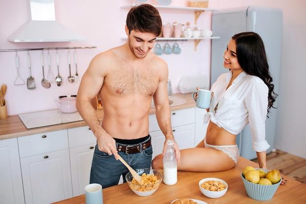 Uomo ben costruito a tavola in cucina. mescola i fiocchi di mais con il latte in una ciotola. la giovane donna sexy si siede sul tavolo e tocca la sua mano.