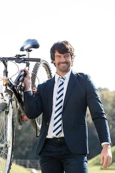 Uomo ben vestito che detengono bicicletta nel parco
