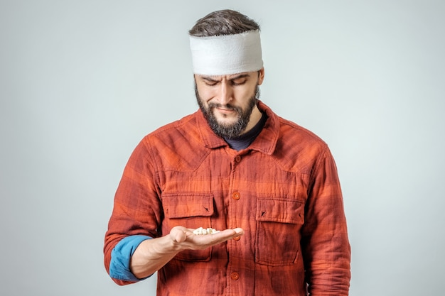 Uomo bendato ferito triste con le pillole