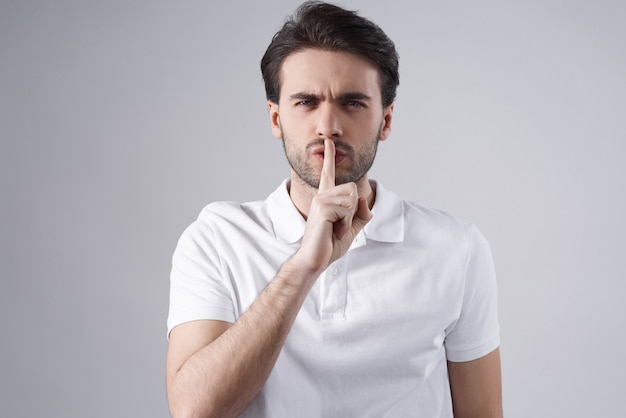 Uomo bianco che posa zittire isolato su fondo bianco.