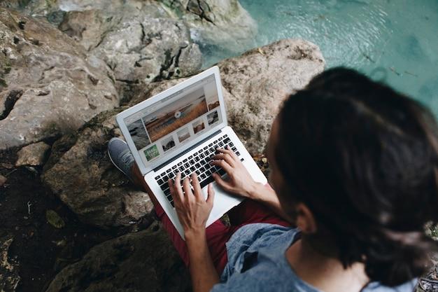 Uomo bianco che utilizza computer portatile del computer alla cascata