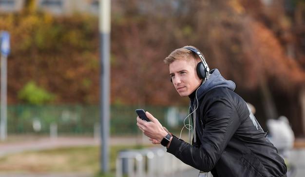 Uomo biondo che ascolta la musica fuori