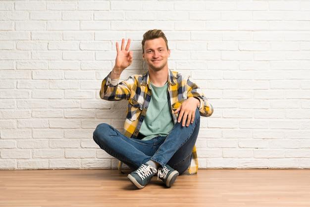 Uomo biondo che si siede sul pavimento felice e che conta tre con le dita