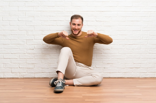 Uomo biondo che si siede sul pavimento fiero e soddisfatto di sé