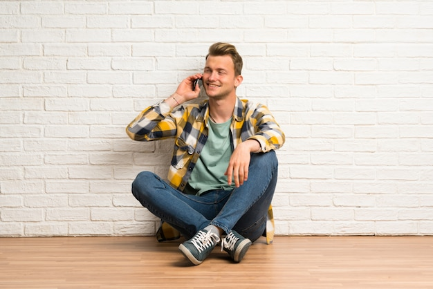 Uomo biondo che si siede sul pavimento mantenendo una conversazione con il telefono cellulare