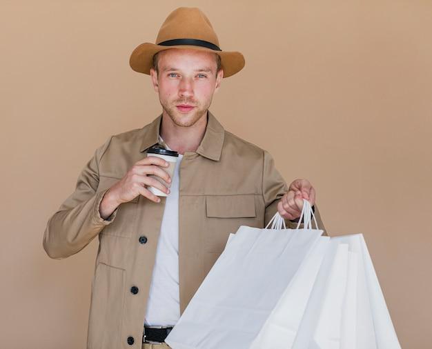 Uomo biondo con i sacchetti della spesa che guardano alla macchina fotografica