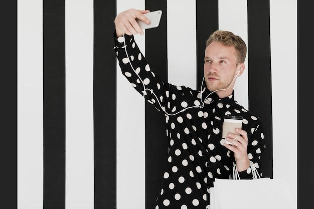 Uomo biondo con la camicia che prende un selfie