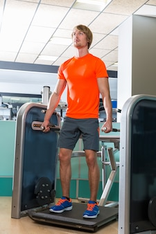 Uomo biondo di allenamento di esercizio della macchina tozza della palestra