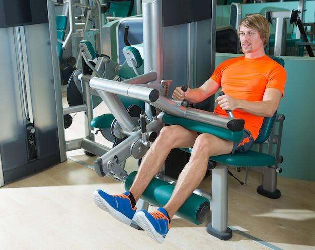 Uomo biondo di esercizio della macchina del ricciolo della gamba messo palestra