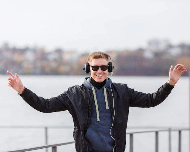 Uomo biondo di smiley del colpo medio che ascolta la musica fuori
