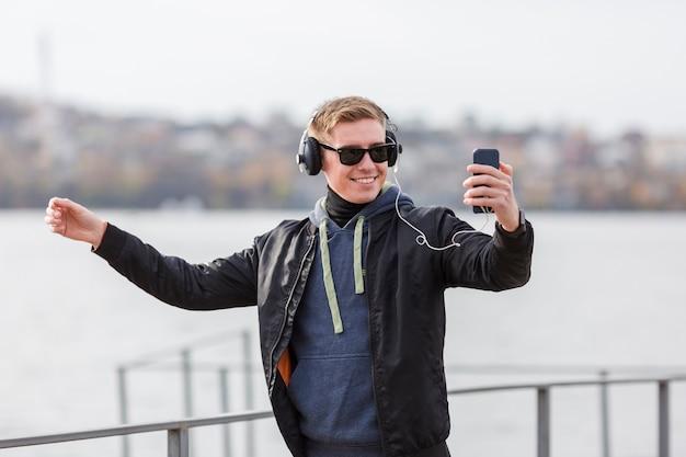 Uomo biondo di smiley di vista frontale che ascolta la musica all'aperto