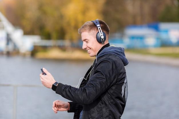 Uomo biondo di smiley lateralmente che ascolta la musica fuori