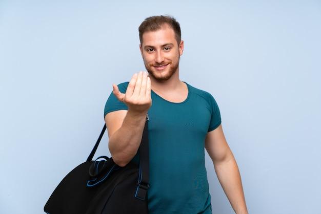 Uomo biondo di sport sopra la parete blu che invita a venire con la mano. felice che tu sia venuto