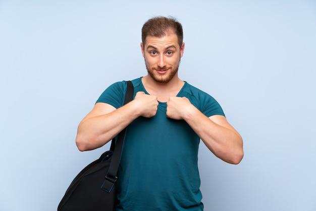 Uomo biondo di sport sopra la parete blu con espressione facciale di sorpresa