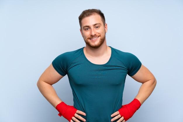 Uomo biondo di sport sopra la parete blu in fasciature di pugilato