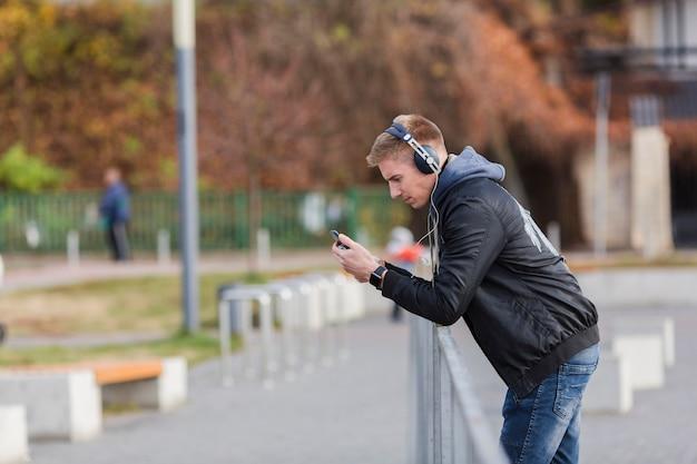 Uomo biondo di vista laterale che ascolta la musica all'aperto