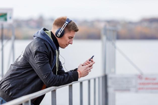 Uomo biondo di vista laterale che ascolta la musica fuori