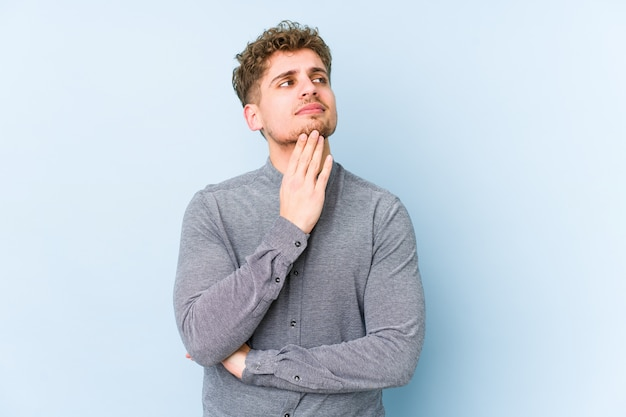 Uomo biondo giovane dei capelli ricci isolato contemplando, progettando una strategia, pensando al modo di fare affari