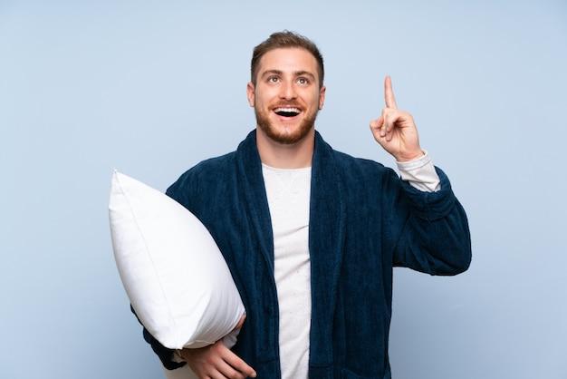 Uomo biondo in pigiama sul muro blu con l'intenzione di realizzare la soluzione sollevando un dito