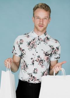 Uomo biondo in sacchetti della spesa della tenuta della camicia in entrambe le mani