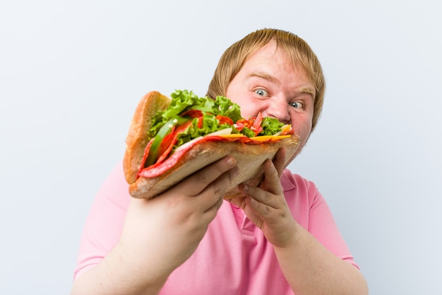 Uomo biondo pazzo caucasico che tiene un panino gigante