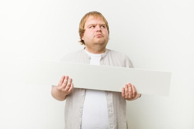 Uomo biondo pazzo caucasico con un cartello
