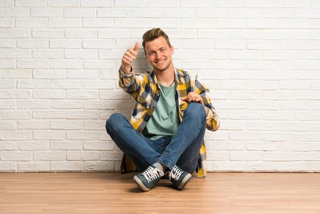Uomo biondo seduto sul pavimento con il pollice in alto perché è successo qualcosa di buono