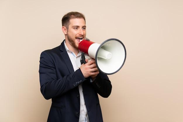 Uomo biondo sopra fondo isolato che grida tramite un megafono