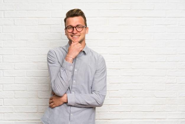 Uomo biondo sopra il muro di mattoni bianco con i vetri e sorridere