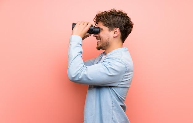 Uomo biondo sopra il muro rosa e guardando in lontananza con il binocolo