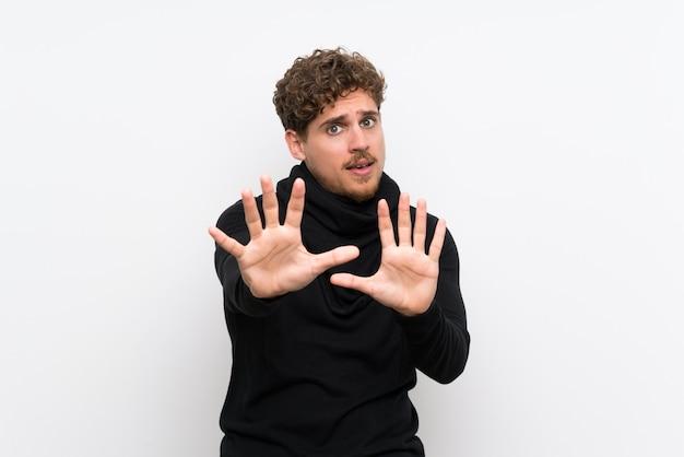 Uomo biondo sopra la parete bianca isolata che allunga nervoso le mani alla parte anteriore