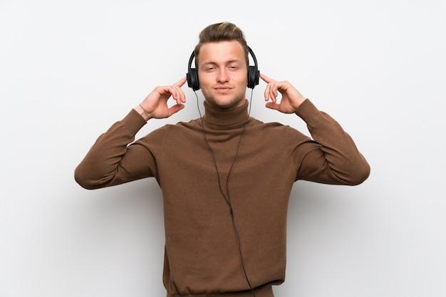 Uomo biondo sopra la parete bianca isolata che ascolta la musica con le cuffie