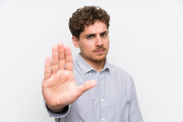 Uomo biondo sopra la parete bianca isolata che fa il gesto di arresto con la sua mano
