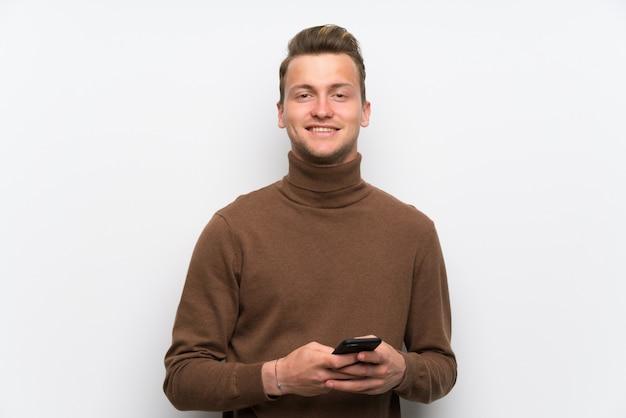 Uomo biondo sopra la parete bianca isolata che invia un messaggio con il cellulare